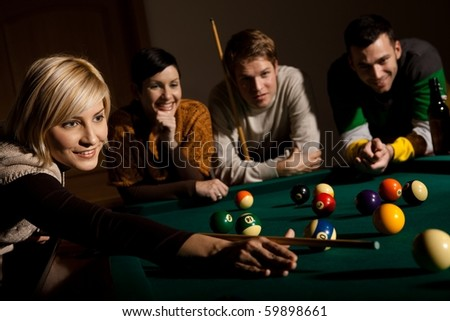Smiling woman aiming at white ball with cue leaning on snooker table, friends watching.? - stock photo