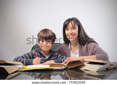 Smiling woman and child doing homework - stock photo