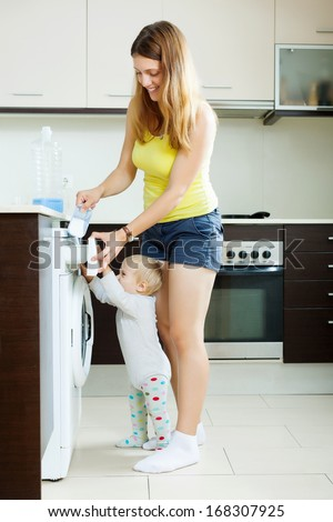 Smiling  woman and child using washing machine with laundry detergent at home - stock photo