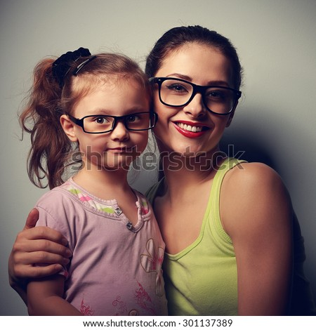 Smiling woman and happy kid girl embracing in fashion eyeglasses and looking happy. Closeup portrait - stock photo