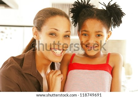 Smiling woman and her little daughter with shaggy hairstyle - stock photo