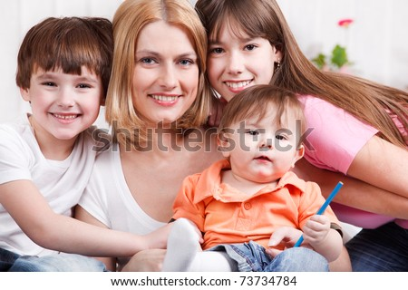 Smiling woman and her three kids - stock photo