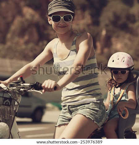 Smiling woman and kid riding in sun glasses. Vintage closeup portrait - stock photo