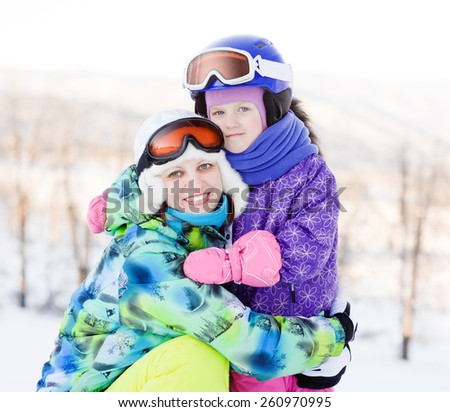 smiling woman and little girl at the ski resort - stock photo