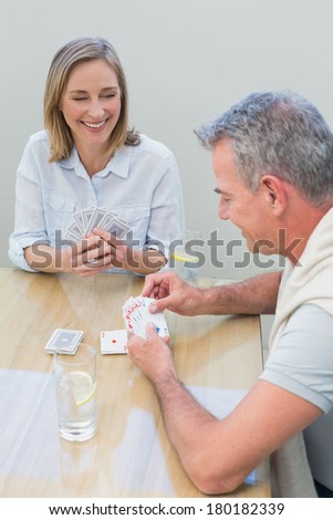 Smiling woman and man playing cards at table in the house - stock photo
