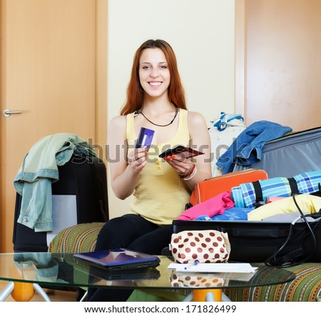 Smiling woman and packing suitcase for  travel - stock photo