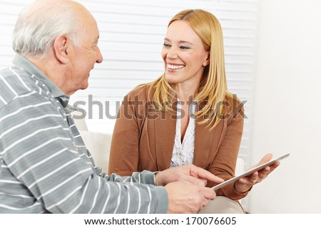 Smiling woman and senior man using tablet computer to surf the internet - stock photo