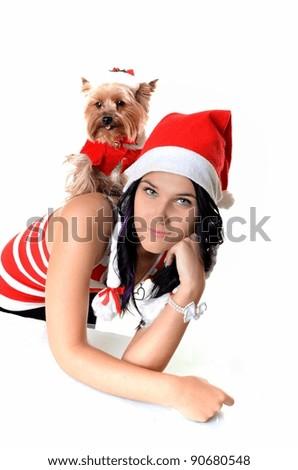 Smiling woman and yorkie, both wearing Santa hats. - stock photo