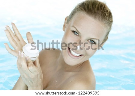 Smiling woman applying cream on her face. Woman in swimming pool. - stock photo