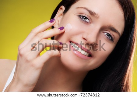 Smiling woman applying moisturizer on her face - stock photo