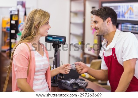 Smiling woman at cash register paying with credit card in supermarket