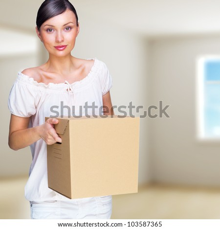 Smiling woman at her home holding boxes. She is Moving at her new home. Mortgage concept - stock photo