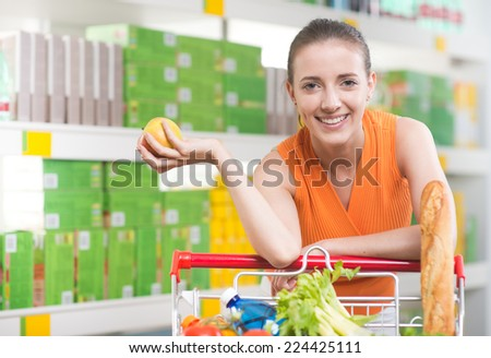 Smiling woman at supermarket holding an apple and leaning to a shopping cart. - stock photo