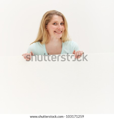 Smiling woman behind blank white board Studio shot of smiling woman behind blank white board on white background