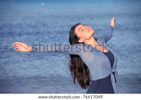 Smiling woman breathing with sea in the background - stock photo