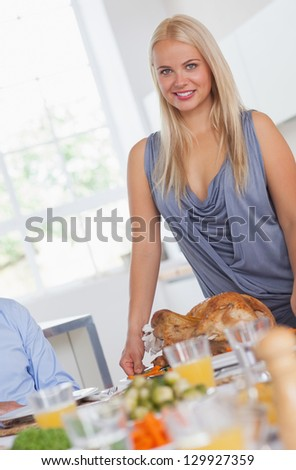 Smiling woman bringing turkey to the table at thanksgiving - stock photo