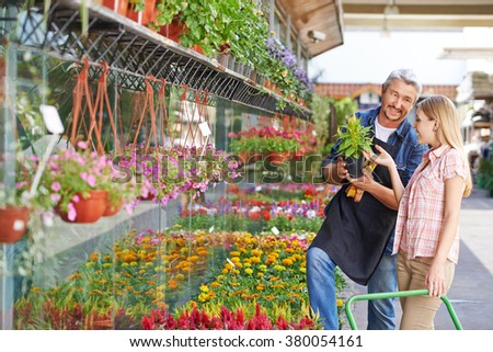 Smiling woman buying yellow woolflower in a nursery shop from a gardener - stock photo