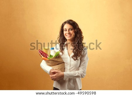 Smiling woman carrying a bag with vegetables in it - stock photo