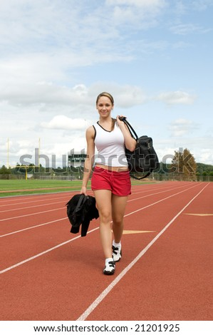 Smiling woman carrying a gym bag and walking on a track. Vertically framed photo.