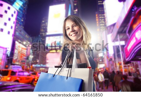 Smiling woman carrying some shopping bags on a city street - stock photo