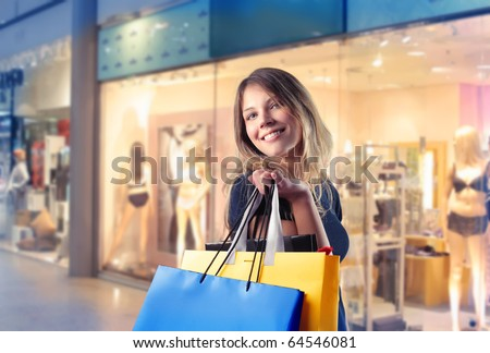 Smiling woman carrying some shopping bags with shops on the background - stock photo