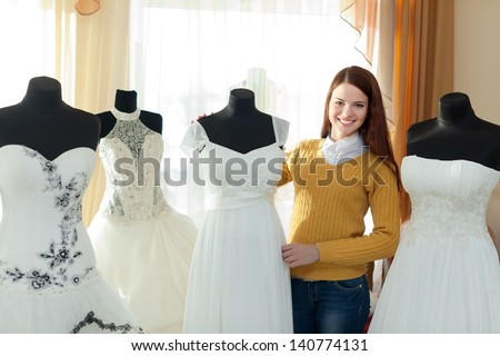 Smiling woman chooses  wedding dress in bridal boutique - stock photo
