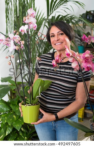 smiling woman choosing a potted phalaenopsis flower in the floral boutique