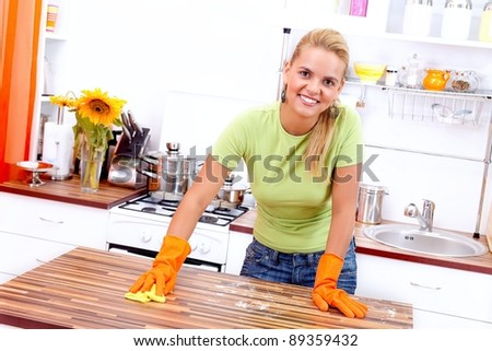 Smiling woman cleaning the kitchen after baking - stock photo