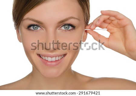 smiling woman cleans ears with cotton sticks isolated on white - stock photo