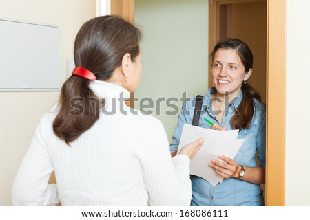 Smiling woman conducting a survey among the population - stock photo