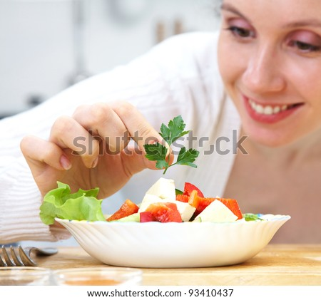 Smiling woman cooking vegetables at kitchen - stock photo