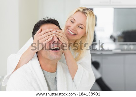 Smiling woman covering happy mans eyes in the kitchen at home - stock photo