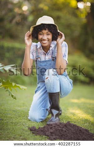 Smiling woman crouching in the garden holding her hat - stock photo