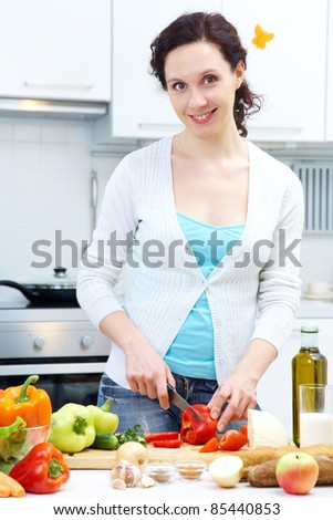 Smiling woman cutting vegetables at kitchen