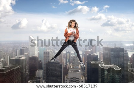 Smiling woman dancing to music with cityscape on the background