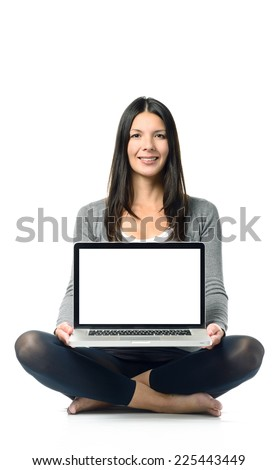 Smiling woman displaying her blank laptop screen to the camera as she sits bare foot and cross-legged on the ground with her computer balanced on her lap over a white background - stock photo