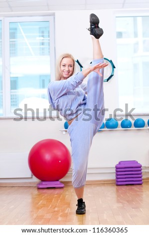 Smiling woman do stretching exercise in sports club. Fitness gym