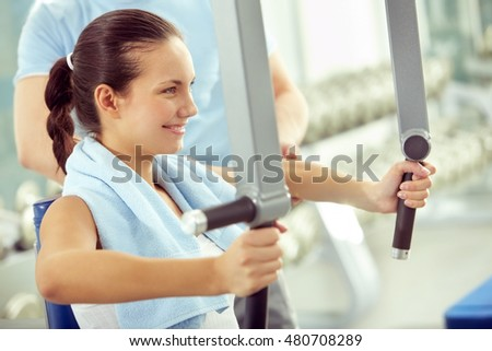 Smiling woman doing exercises on sport machine