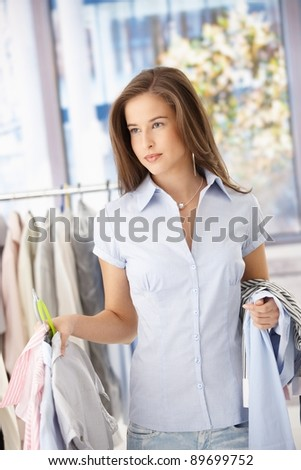 Smiling woman doing shopping, holding clothes, standing in store.? - stock photo