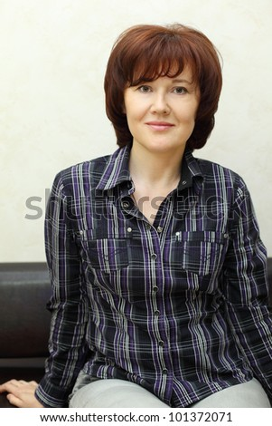 smiling woman dressed in checkered shirt sits on black leather couch - stock photo