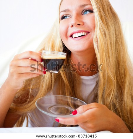 Smiling woman drinking a coffee lying on a sofa at home - stock photo