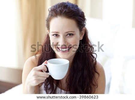 Smiling woman drinking a cup of coffee in bedroom in the morning - stock photo