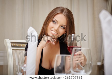 Smiling woman drinking aperitif in restaurant - stock photo