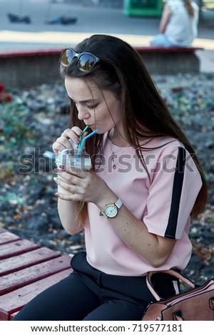 Smiling woman drinking cappuccino outdoors holding plastic cup