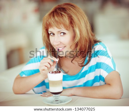 Smiling woman drinking coffee smiling at camera - stock photo