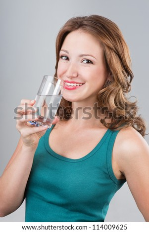 Smiling woman drinking water on grey background. Young woman holding glass of water. Studio shot - stock photo