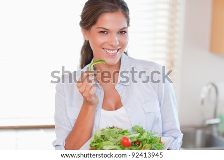 Smiling woman eating a salad in her kitchen - stock photo