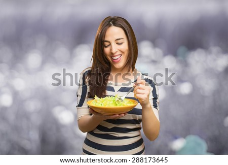 Smiling woman eating a salad. Over abstract background