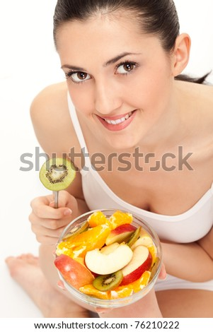smiling woman eating trusty salad, close up, isolated on white - stock photo