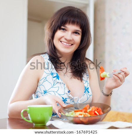 Smiling woman eats vegetables salad at home
